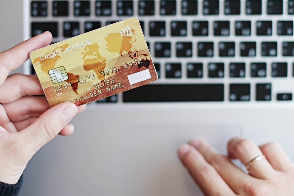 Person using a credit card to shop online on a B2C website. Does my business need a B2B or a B2C website?