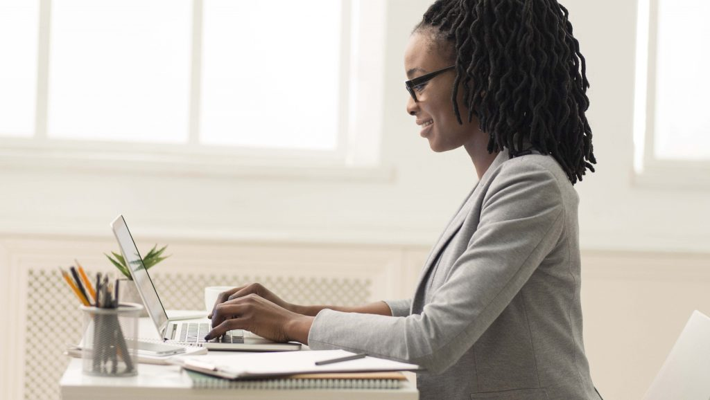 Female using a laptop to create a digital marketing campaign in order to improve climate change.