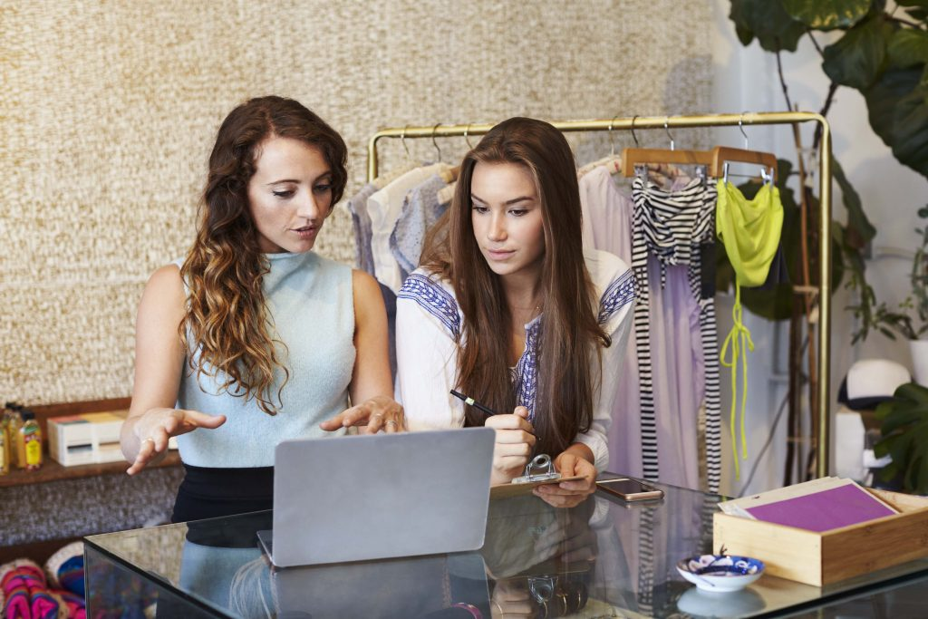 Retail Store Need a Website. Two women looking though an online catalog of a clothing retail store.  Online shopping.
